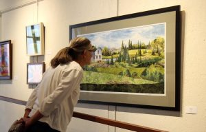 photo of woman examining painting of landscape